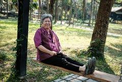 Une femme plus âgée se reposant dans le jardin détente femelle pluse âgé sur l'oscillation Photographie stock
