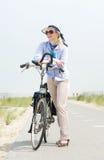 Une femme plus âgée se tenant avec la bicyclette sur le chemin le jour d'été Photos libres de droits