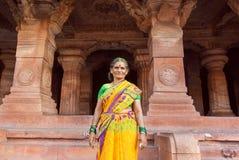 Une femme plus âgée souriant à l'intérieur du temple hindou du 6ème siècle avec les colonnes découpées de Karnataka antique Images libres de droits