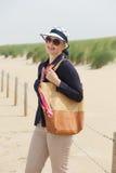 Une femme plus âgée souriant à la plage avec les lunettes de soleil et le sac Photo stock