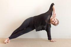 Une femme plus âgée souriant dans la posture de côté de yoga photos stock