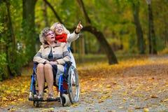 Une femme plus âgée sur le fauteuil roulant avec la jeune femme en parc Photo libre de droits