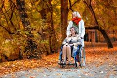Une femme plus âgée sur le fauteuil roulant avec la jeune femme en parc Images stock
