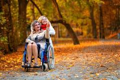 Une femme plus âgée sur le fauteuil roulant avec la jeune femme en parc Image stock
