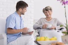 Une femme plus âgée sur un fauteuil roulant avec la tasse de thé Photos stock