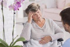 Une femme plus âgée sur un fauteuil roulant avec le mal de tête Photo libre de droits