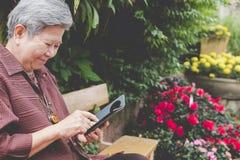 une femme plus âgée tenant le téléphone portable dans le jardin texti femelle plus âgé Photographie stock libre de droits