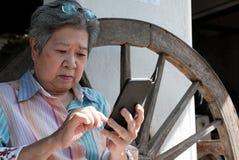 une femme plus âgée tenant le téléphone portable dans le jardin texti femelle plus âgé Images libres de droits