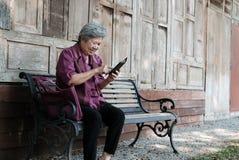 une femme plus âgée tenant le téléphone portable dans le jardin texti femelle plus âgé Image libre de droits