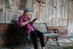 une femme plus âgée tenant le téléphone portable dans le jardin texti femelle plus âgé Images stock