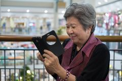 Une femme plus âgée tenant le téléphone portable dans le magasin Fe plus âgé Photos stock