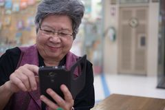 Une femme plus âgée tenant le téléphone portable dans le magasin Fe plus âgé Image stock
