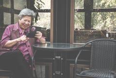 Une femme plus âgée tenant le téléphone portable sur la terrasse texte femelle plus âgé Image stock