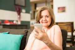 Une femme plus âgée tenant son téléphone Photos libres de droits