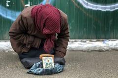 Une femme pluse âgé et sans abri demande la pitié des passants indifférents Le concept de la pauvreté, indifférence, solitude images stock