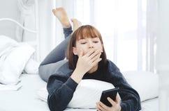 Une femme portant une robe noire se repose dans sa chambre Et elle est jeu mobile photos stock