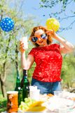 Une femme posant en robe rouge et grands verres de soleil drôles sur la PA de jardin images libres de droits