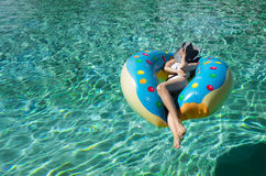 Une femme pose au-dessus d'une piscine claire d'aqua photo stock