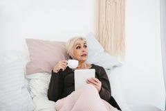 Une femme positive boit d'un café de matin se situant dans le lit et utilise un comprimé pour observer des vidéos, pour écouter l Photos stock