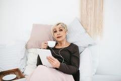 Une femme positive boit d'un café de matin se situant dans le lit et utilise un comprimé pour observer des vidéos, pour écouter l Photos libres de droits