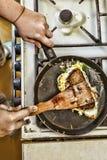 Une femme prépare le petit déjeuner à la maison dans la cuisine Pains grillés dans une poêle avec le vert et le lard d'oeufs Nour photos libres de droits