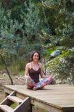Une femme pratique le yoga sur le porche d'une vieille maison en bois photos libres de droits