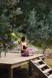 Une femme pratique le yoga sur le porche d'une vieille maison en bois photographie stock