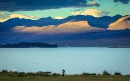 Une femme prenant la photo sur le lac de turquoise Photo libre de droits