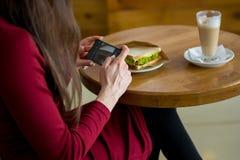 Une femme prend une photo d'un sandwich et d'un latte dans un café Photographie stock libre de droits