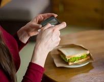 Une femme prend une photographie d'un sandwich dans un café Image stock