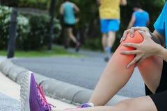 Une femme pulsante a la douleur de genou Est un problème avec l'inflammati de genou photographie stock