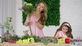 Une femme rassemble un bouquet des fleurs et une fille dessine dans des crayons colorés banque de vidéos