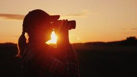 Une femme regardant par des jumelles le coucher du soleil Concept de voyage et de safari Photo libre de droits