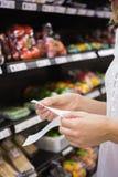 Une femme regardant sa liste d'épicerie Image stock