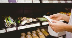 Une femme regardant sa liste d'épicerie Photos libres de droits