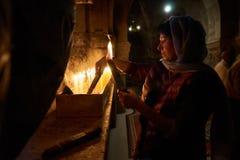 Une femme regarde un groupe allumé de 33 bougies images stock