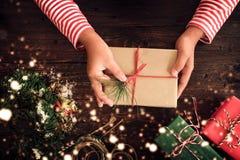 Une femme remet tenir un cadeau de Noël avec un ruban rouge et la neige plus de sur une table en bois images stock