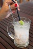 Une femme remuant le jus de noix de coco avec la paille Image stock