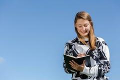 Une femme riant et prend des notes Photographie stock