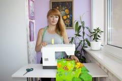 Une femme rousse et sa machine à coudre Aimez votre lieu de travail Image stock