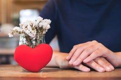 Une femme s'asseyant avec le signe de coeur et le vase à fleur rouges sur la table en bois Photos stock
