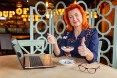 Une femme s'asseyant dans un café, mangeant un dessert et montrant la rétroaction manient maladroitement  image stock