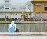 Une femme s'asseyant et priant au temple d'or à Amritsar, Inde Photos libres de droits