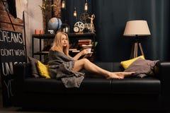 Une femme s'asseyant sur le divan avec une tasse dans des ses mains et souriant comme elle regarde devant elle images stock