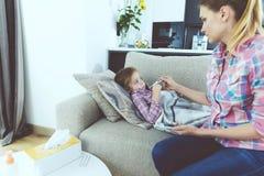 Une femme s'assied à côté d'une petite fille qui est malade Elle donne à la fille un thermomètre pour mesurer sa température Photo libre de droits