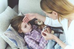 Une femme s'assied à côté d'une petite fille qui est malade Elle tient un thermomètre, que la température du ` s de fille a mesur Images libres de droits