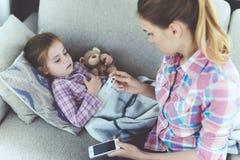 Une femme s'assied à côté d'une petite fille qui est malade Elle tient un thermomètre, que la température du ` s de fille a mesur Images stock