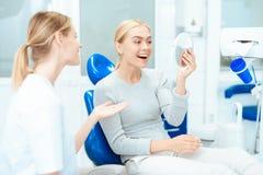 Une femme s'assied à une réception du ` s de dentiste Elle regarde dans le miroir ses dents Sourire de femme photos libres de droits