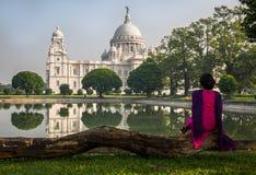 Une femme s'assied au jardin architectural de bâtiment de Victoria Memorial près du lac du sud Image libre de droits