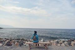 Une femme s'assied sur le banc photographie stock libre de droits